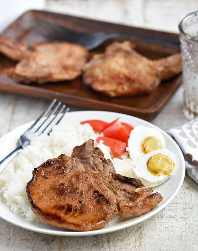 filipino-style pork chops with calamansi flavor on a white plate with steamed rice, chopped tomatoes, and salted eggs