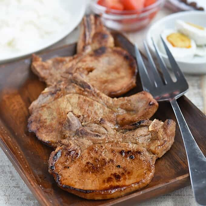 Toyomansi Pork Chops on a wooden platter with steamed rice, chopped tomatoes, and salted eggs on the side