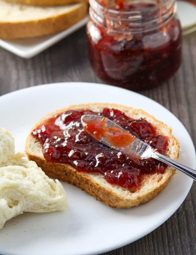 wheat toast with black pepper strawberry jam on a white plate with jar of jam on the side