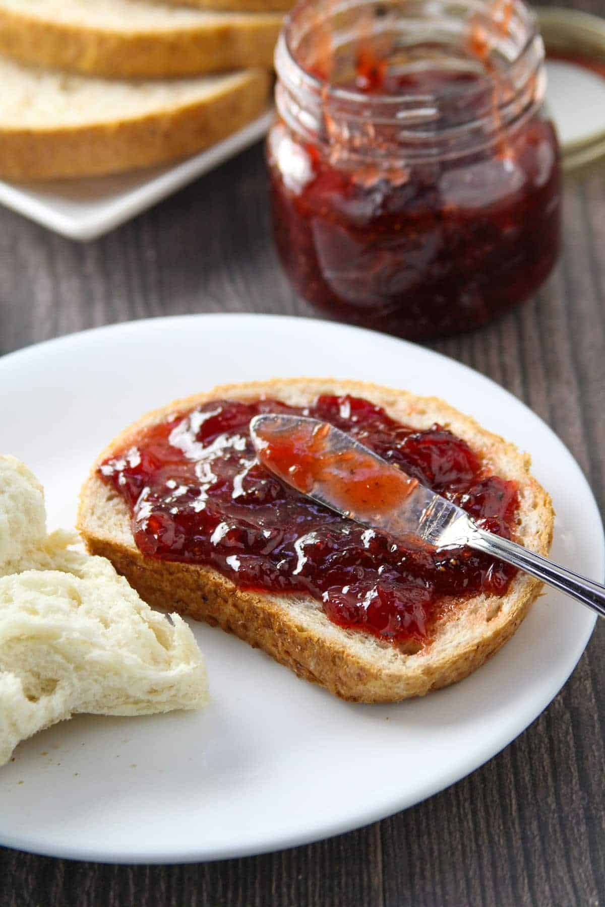 wheat toast with black pepper strawberry jam on a white plate with a jar of jam on the side