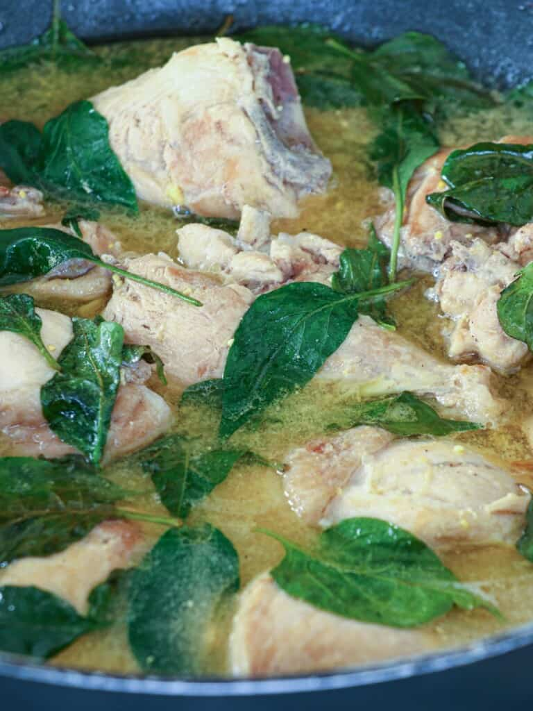 Filipino chicken soup with fish sauce and chili leaves in a pot