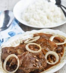 pork bistek garnished with onion rings on a serving platter with a plate of steamed rice on the side