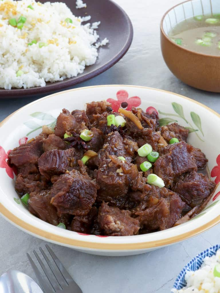 Beef Pares in a serving bowl with a plate of sinangag and broth on the side