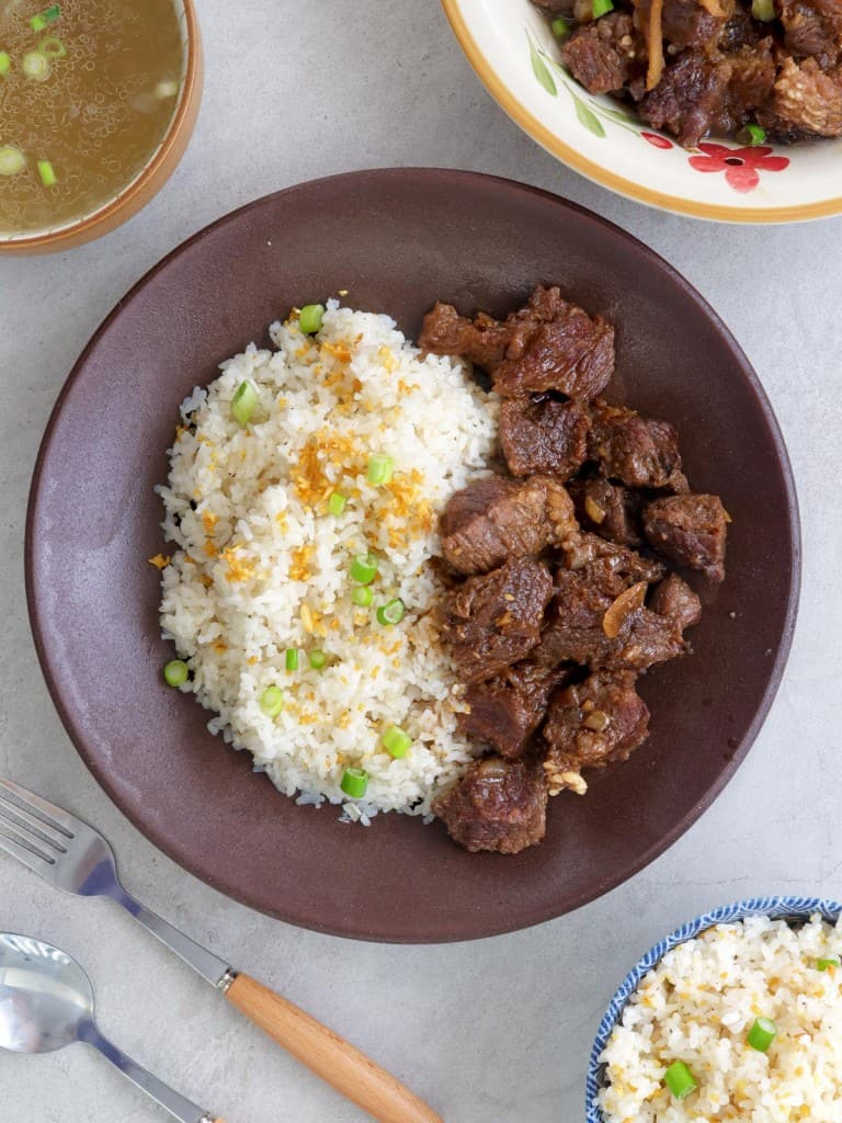 braised beef and garlic fried rice in a brown bowl with a bowl of broth on the side