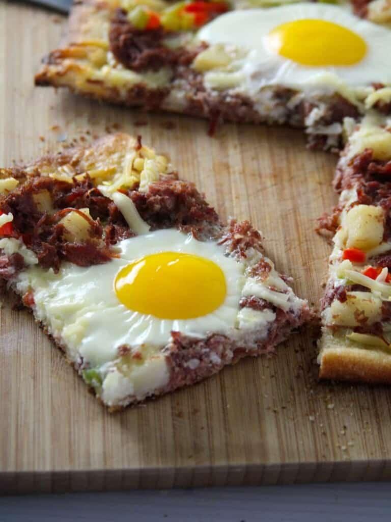 slice of breakfast pizza on a cutting board