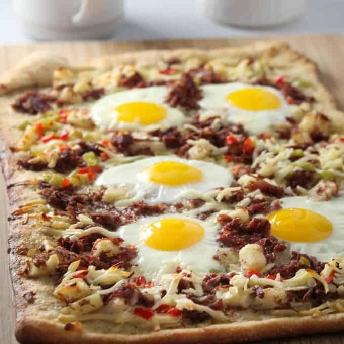 Corned Beef Hash Breakfast Pizza on a wooden board