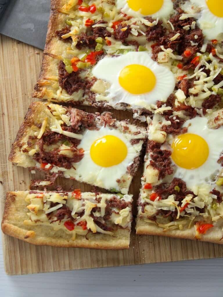 sliced breakfast pizza with egg and corned beef hash topping
