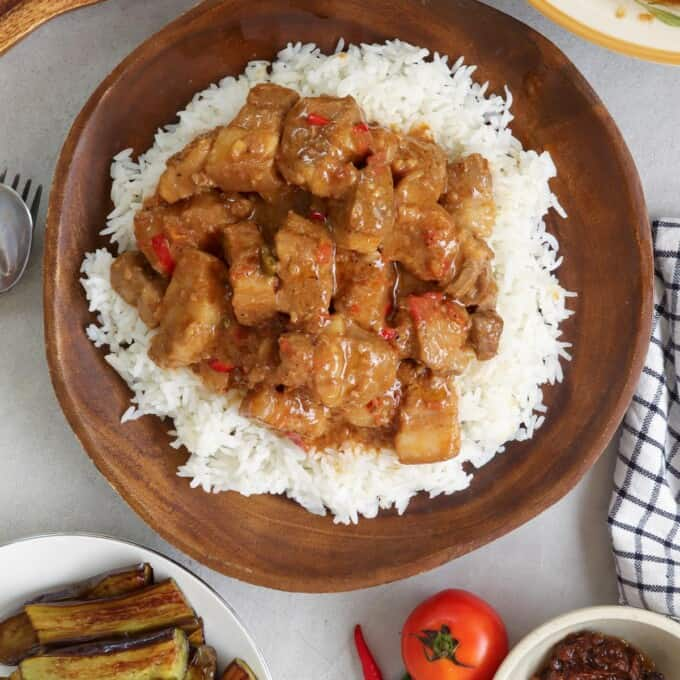 Pork Binagoongan with coconut milk over rice on a wooden plate
