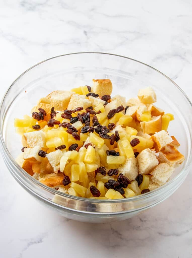 cubed bread, raisins, pineapples in a bowl