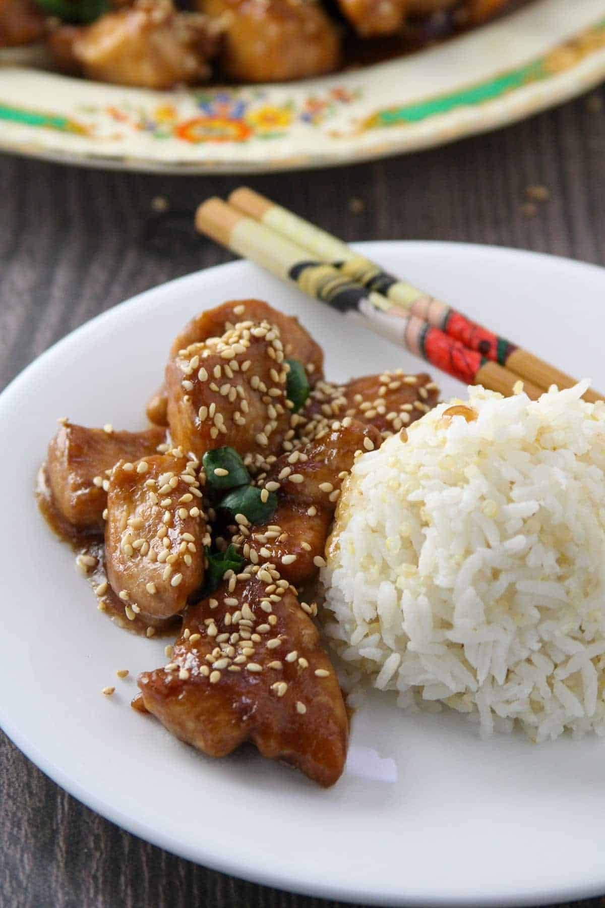 Sesame Chicken with steamed rice on a white plate