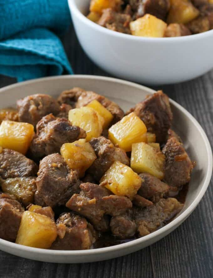 pork adobo with pineapple in a white serving bowl