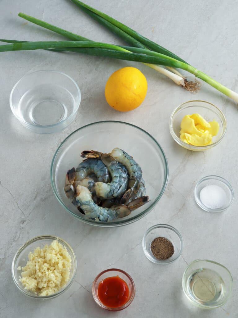 peeled shrimp, lemon, green onions, minced garlic, salt, pepper, sriracha sauce in individual bowls