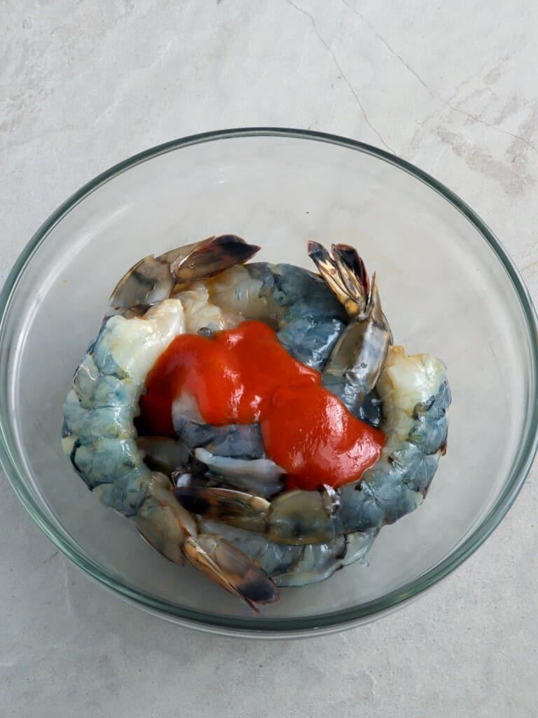 peeled shrimp marinating in Sriracha sauce in a glass bowl