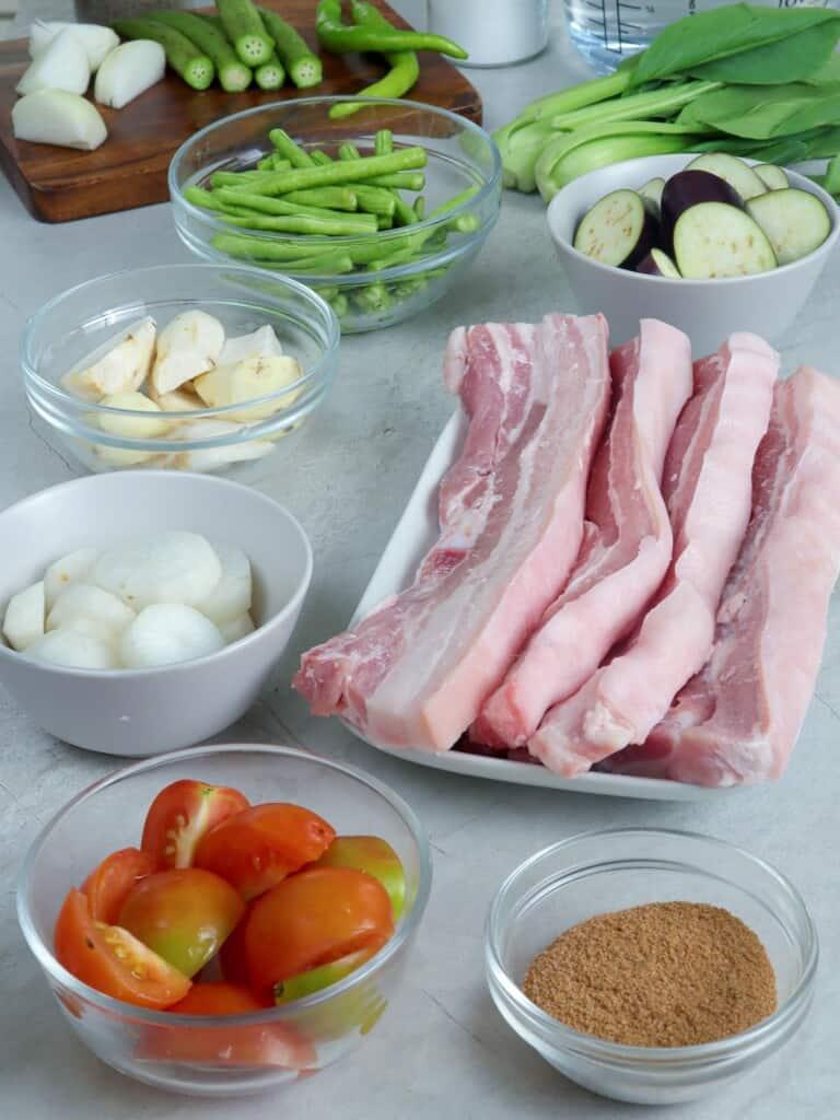 pork belly strips, pechay, eggplant, onions, tomatoes, gabi, tamarind powder, okra, sitaw, radish