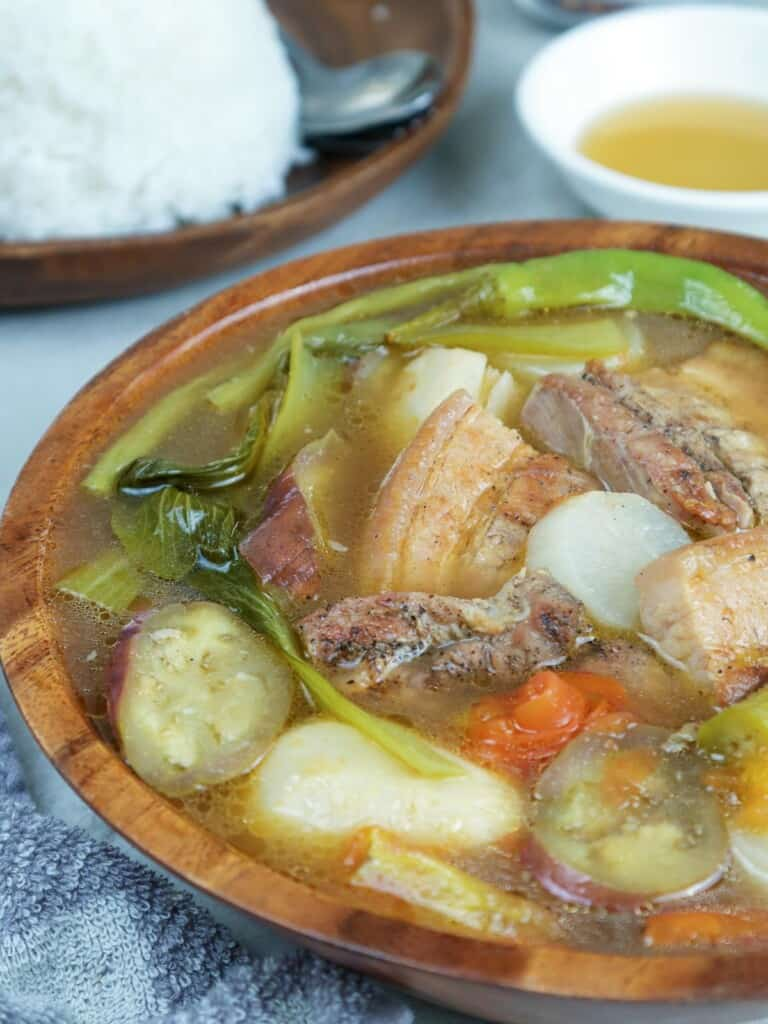 sinigang with grilled pork belly in a serving bowl with a side of steamed rice and fish sauce