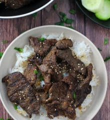 beef bulgogi over steamed rice on a white plate
