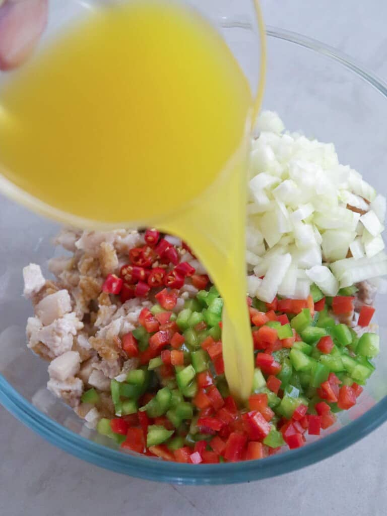 pouring calamansi juice to a bowl of sisig