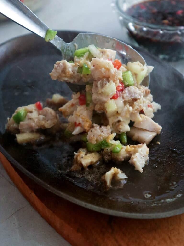 putting sisig on a sizzling plate