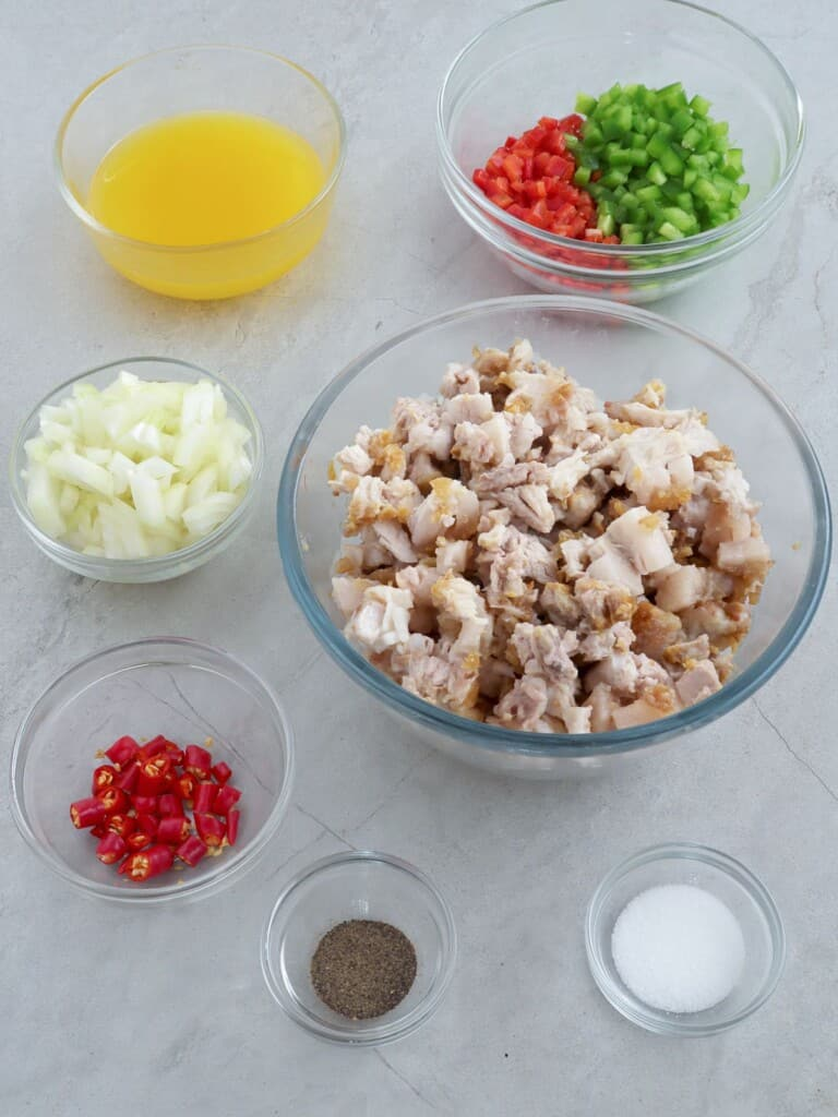 chopped lechon kawali, bell peppers, onions, chili peppers, lemon juice, salt, and pepper in individual bowls