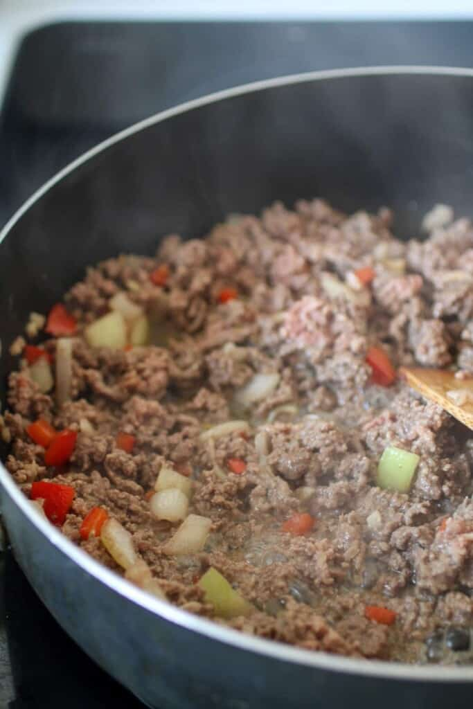 browning ground beef in a skillet with onions and bell peppers