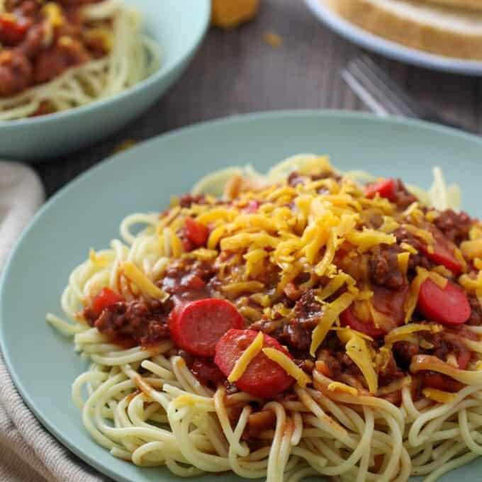 Filipino Spaghetti with hot dogs and grated cheese on a serving plate