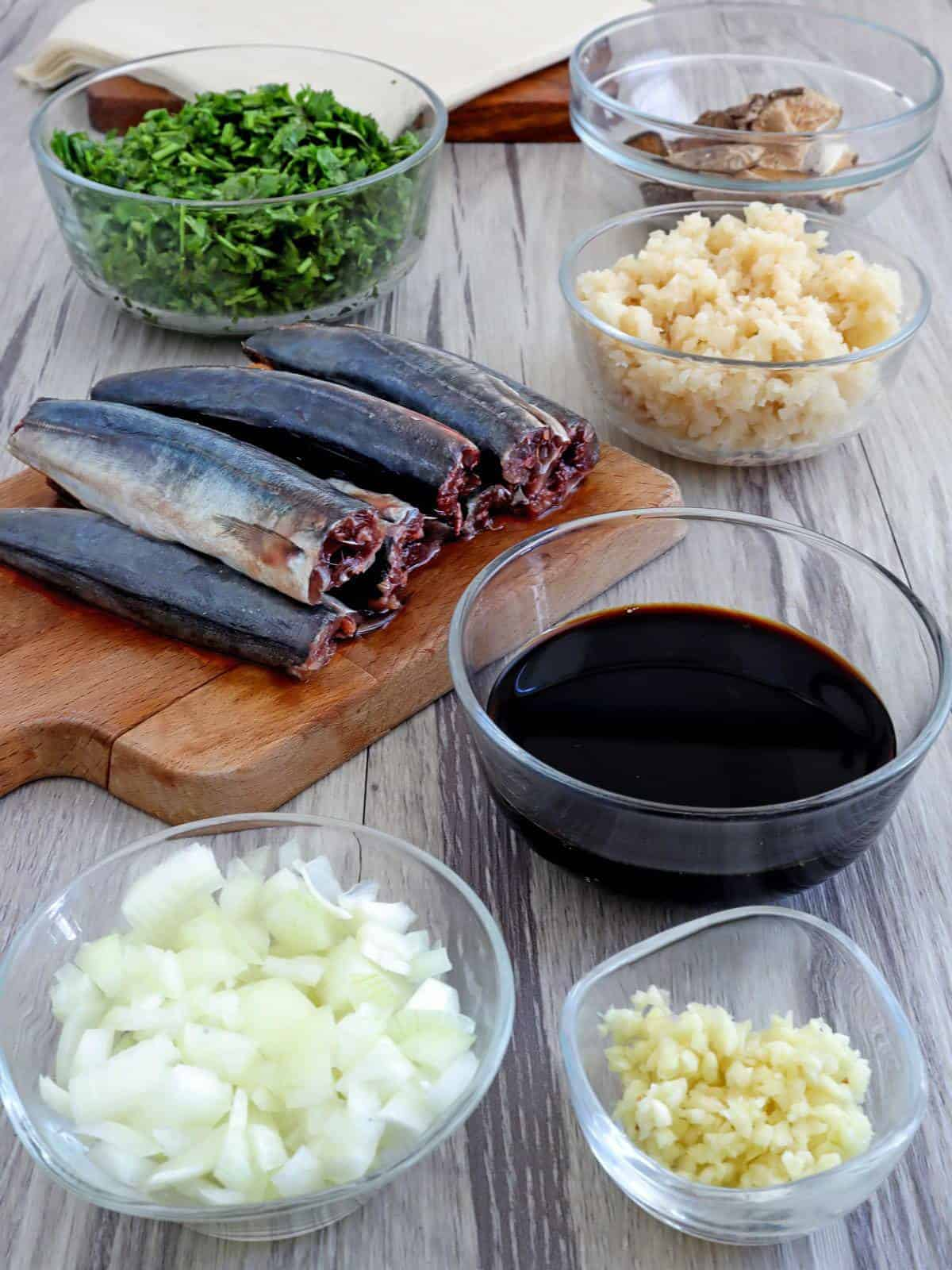 cleaned round scad fish on a cutting board and soy sauce, chestnuts, onions, Chinese celery, garlic in individual bowls