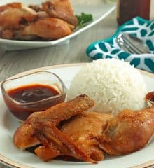 cut-up fried chicken with steamed rice on a white plate