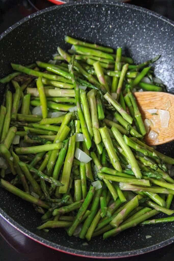 stir-frying asparagus in a wok