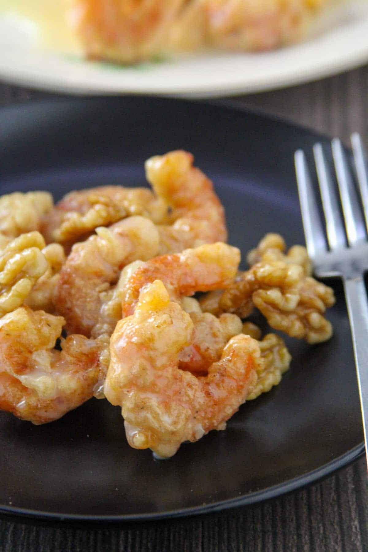 Honey Walnut Shrimp on a black serving plate with a fork