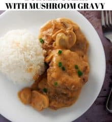 burger steak with mushroom gravy and steamed rice on a white plate