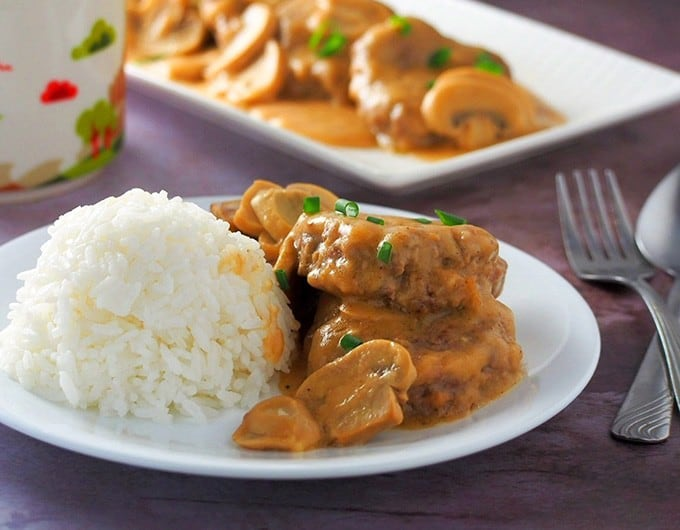 burger steak smothered with mushroom gravy with steamed rice on the side on a white serving plate