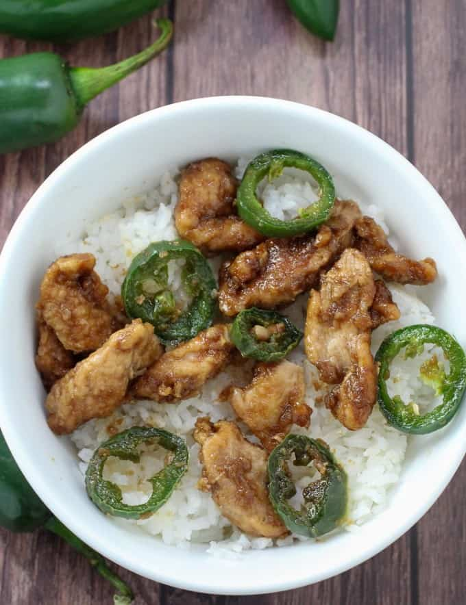 stir-fried chicken with jalapenos over steamed rice in a white bowl