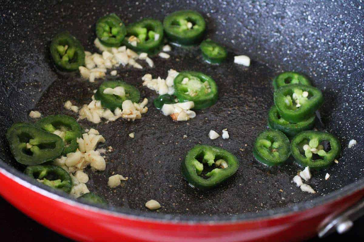 sauteing garlic and jalapeno in a red skillet