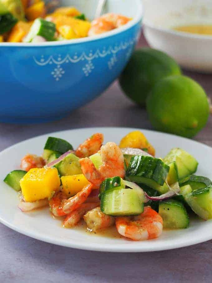 mango avocado cucumber salad with grilled shrimp on a white serving plate