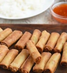 fried lumpiang shanghai on a wooden platter with a plate of steamed rice and small bowl of sweet chili sauce on the side