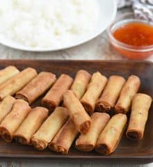 fried lumpiang shanghai on a wooden serving platter with a plate of steamed rice and a small bowl of sweet chili sauce on the side