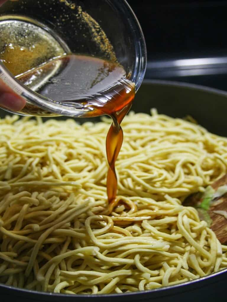 pouring seasoning sauce to a pan of noodles