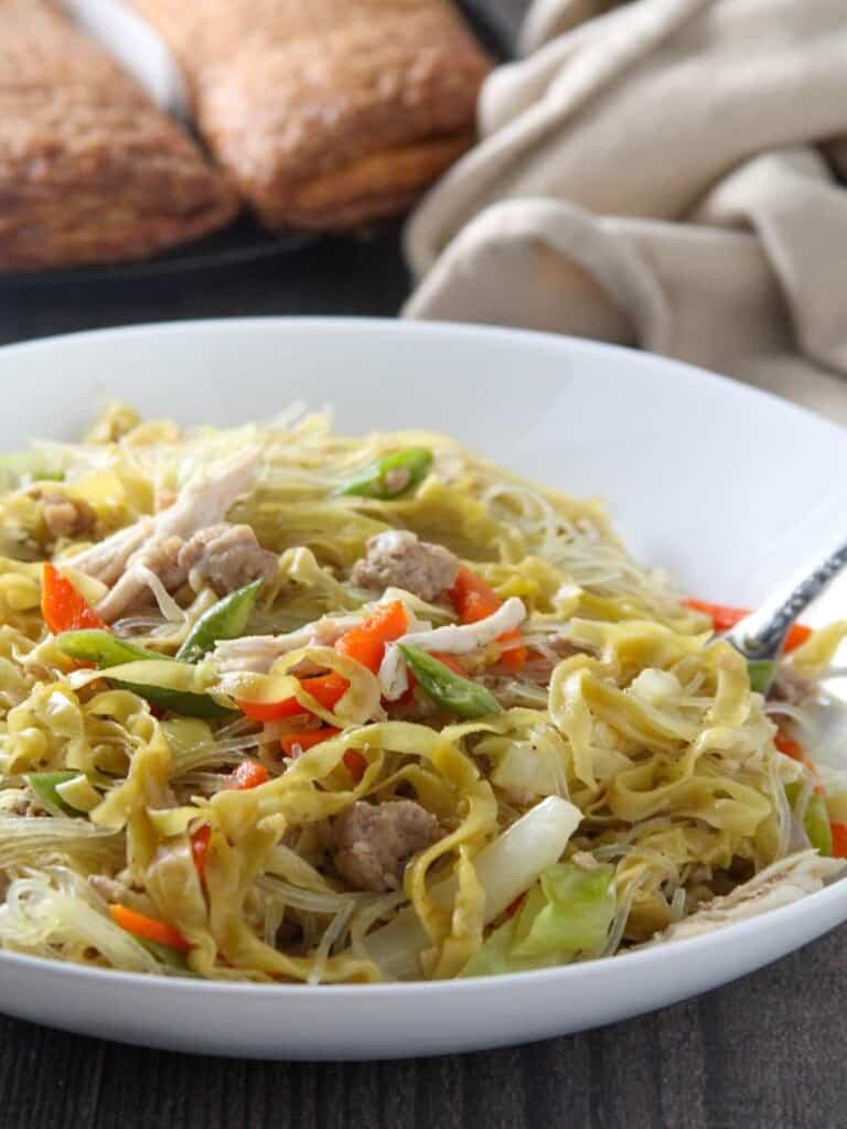 eating pancit langlang from a white bowl