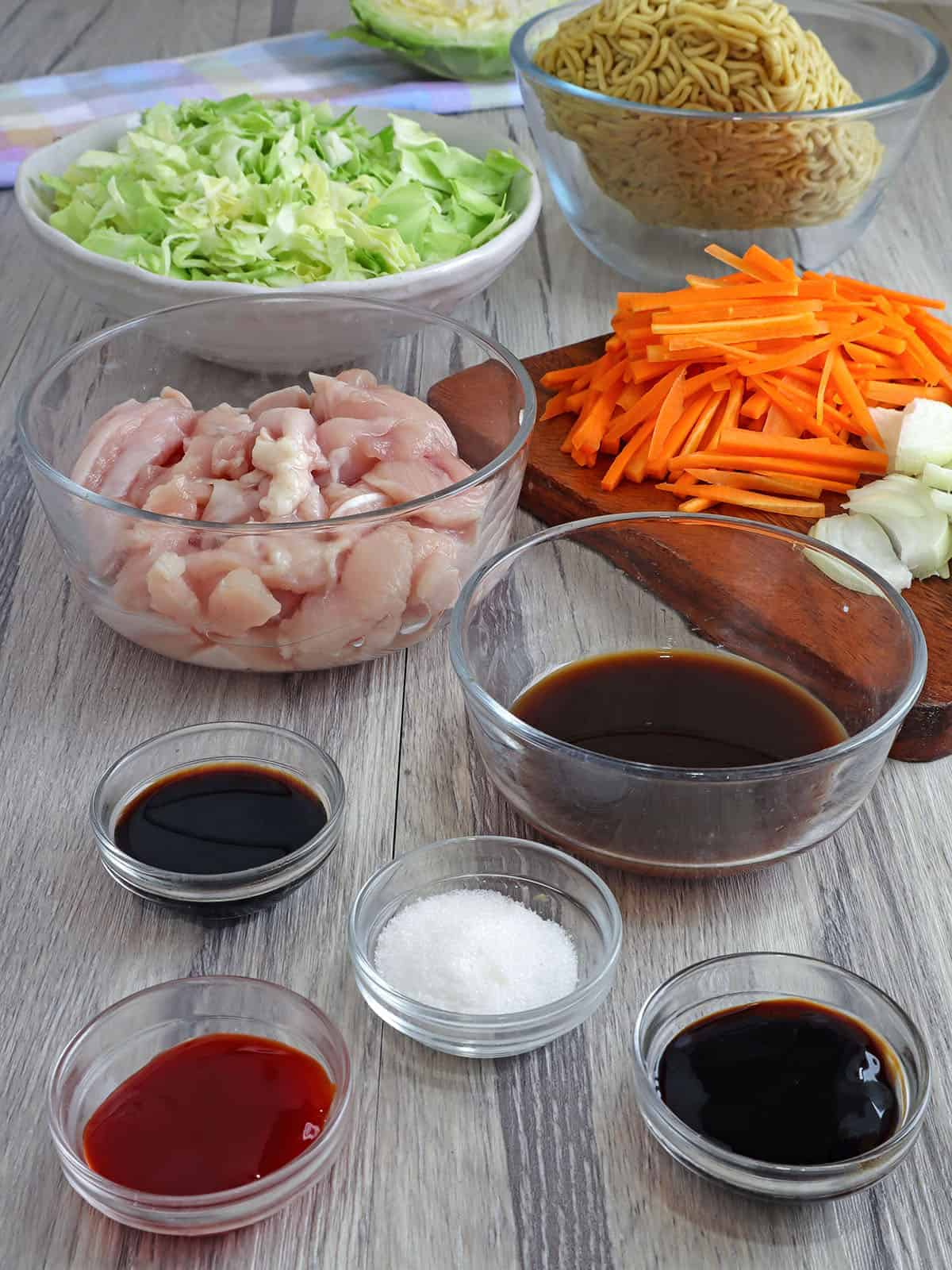 egg noodles, diced chicken breasts, julienned carrots, shredded cabbage, sauces in bowls