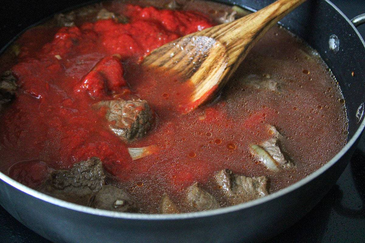 stirring tomato sauce with the beef and broth in a pan