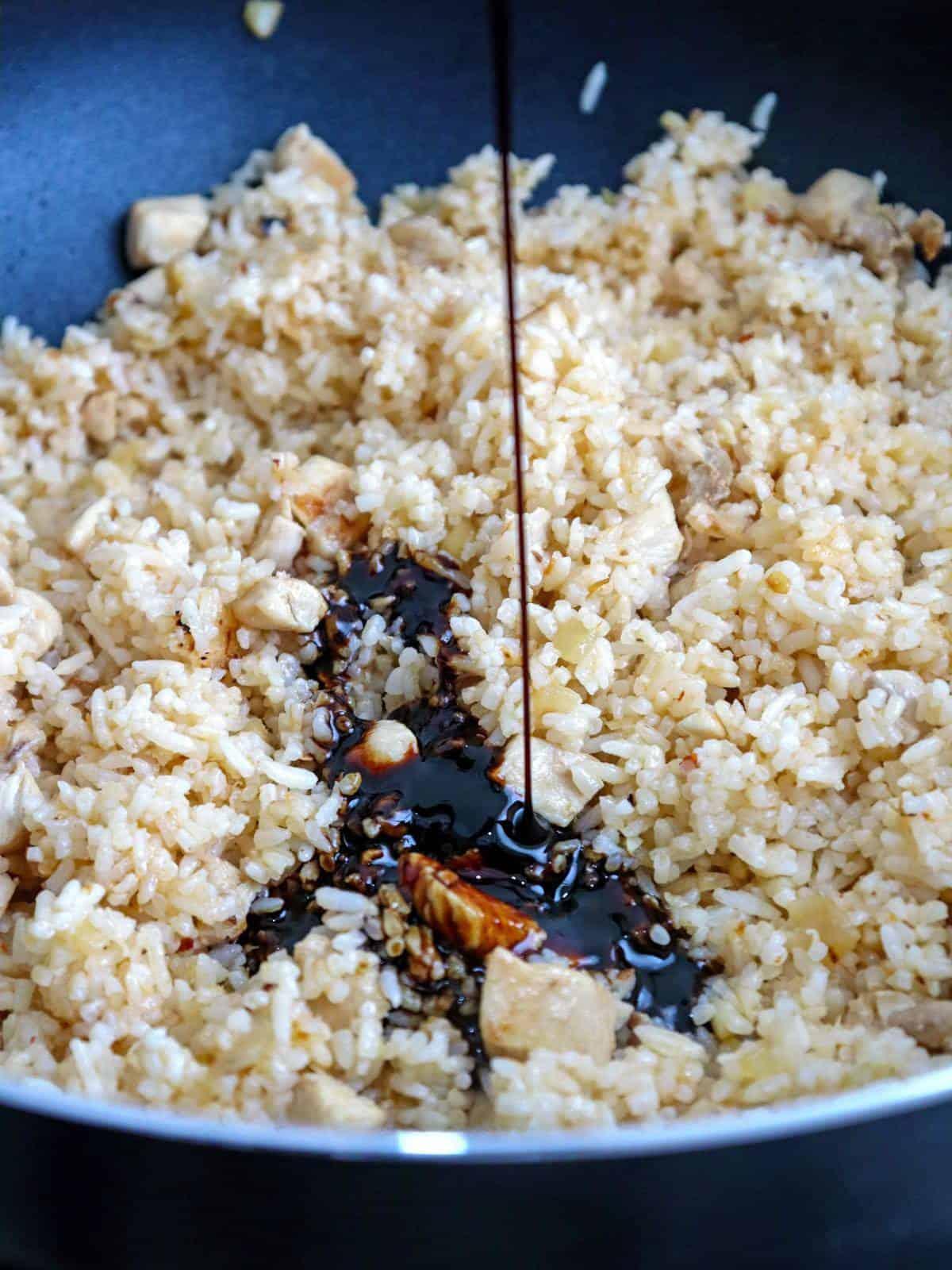 adding kecap manis to fried rice in a pan