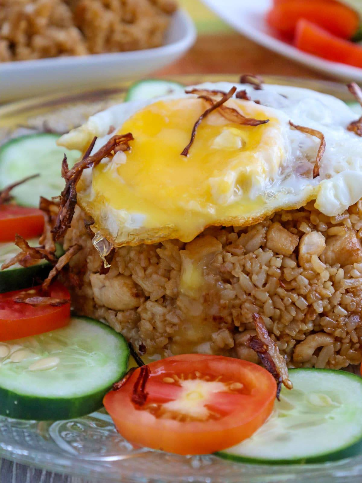 Indonesian fried rice topped with fried egg and garnished with sliced tomatoes and cucumber on a serving plate