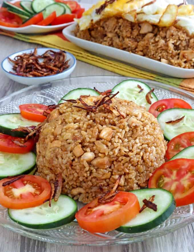 Nasi Goreng on a plate garnished with sliced tomatoes and cucumber