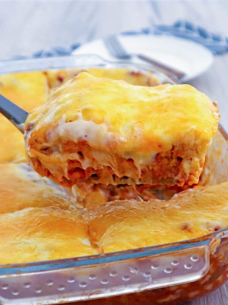 serving Cheesy lasagna with bechamel sauce layers from a baking dish with a spatula