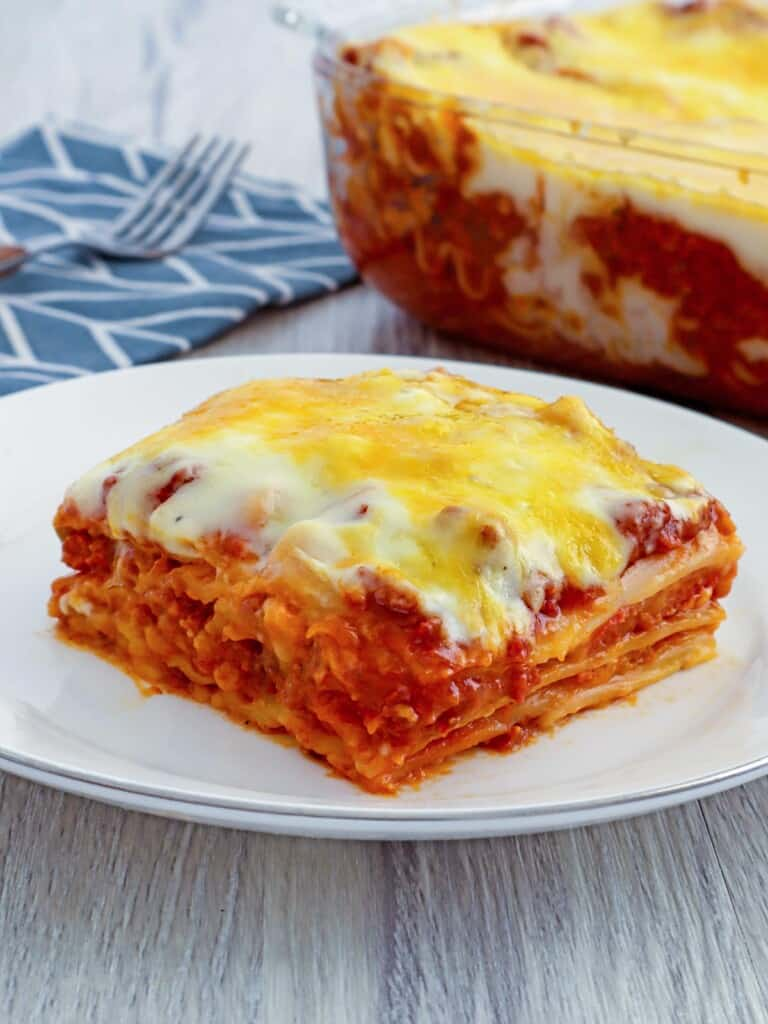 Cheesy lasagna with bechamel sauce layers from a baking dish with a spatula