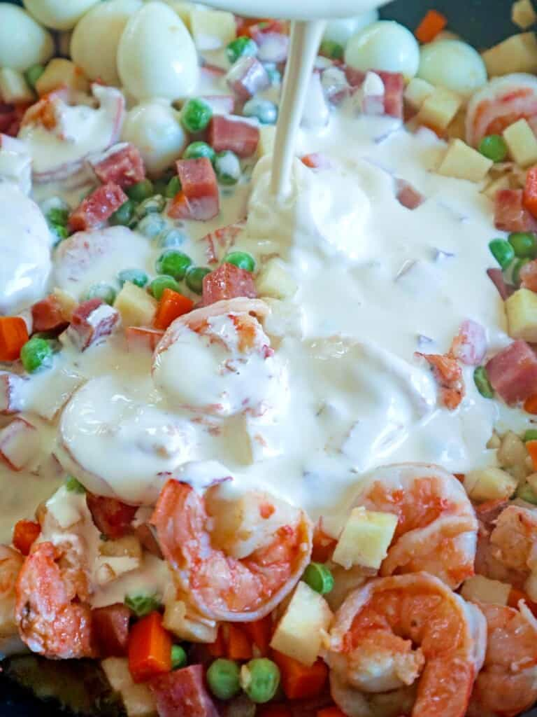 pouring cream on sauteed shrimp and mixed veggies