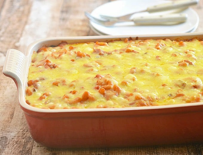 Baked Macaroni with Chicken and cheese topping in a red baking dish