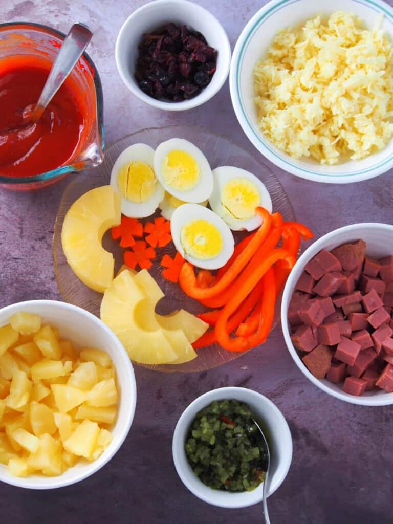 hard-boiled eggs, pineapple tidbits, sliced bell peppers, tomato sauce, shredded cheese, sweet pickles, raisins