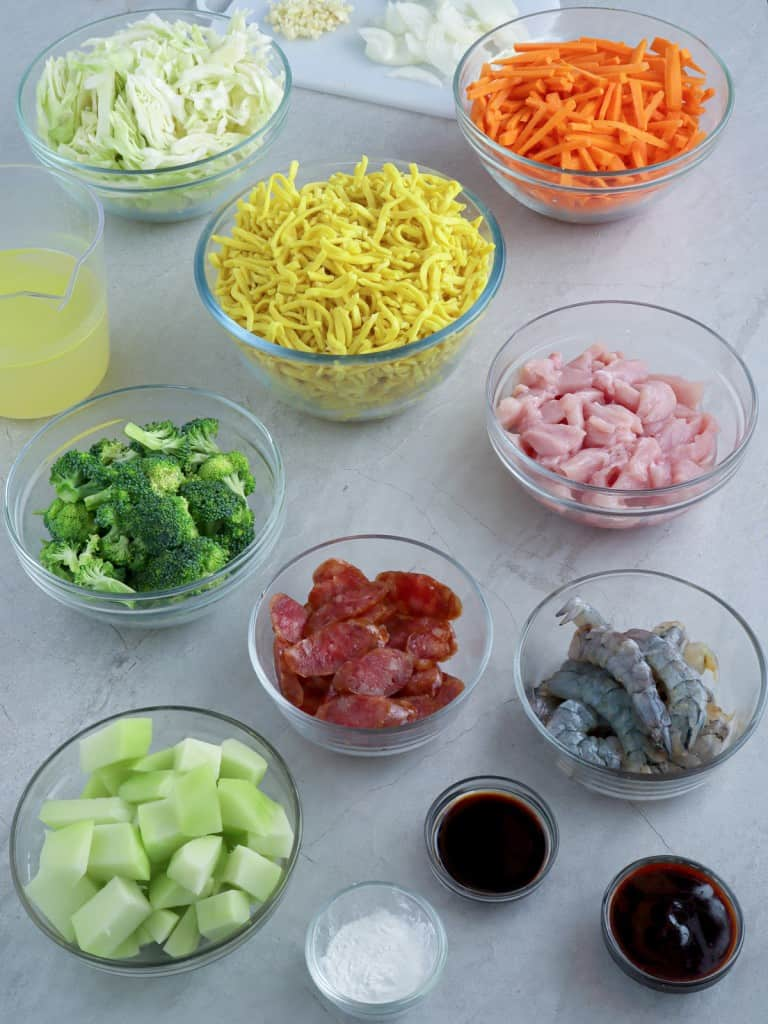 lomi noodles, sliced chicken breasts, broccoli florets, peeled shrimp, julienned carrots, chopped onions, sliced chayote, sliced Chinese sausage in individual bowls