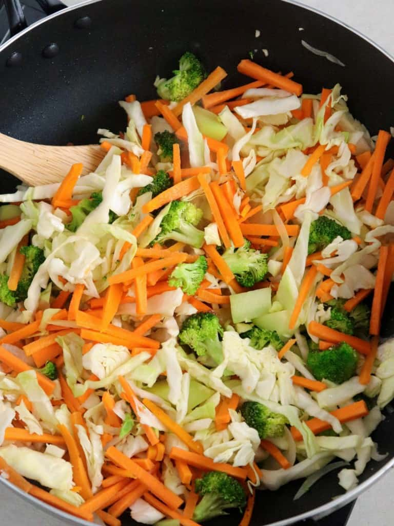 stir-frying assorted vegetables in a skillet